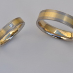 Tr29 - Combinatie witgoud-geelgoud, met in de damesring een vierkante diamant van 0,07 karaat